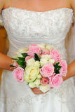 Bride dress and flower detail. Close up of brides dress and bouquet at wedding Royalty Free Stock Photo
