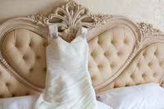 Bride dress. A bride dress hanged from a beautifull bed Royalty Free Stock Photography