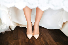 Bride in a dress and beige shoes is standing on a wooden floor. Close-up Stock Images