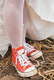 Bride in dress in red plimsolls on ground Royalty Free Stock Images