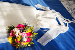 Bride dress and wedding bouquet lie on the bed Stock Images