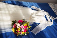 Bride dress and wedding bouquet lie on the bed Royalty Free Stock Images
