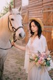 Cowboy style bride standing near horse, close up stock photo