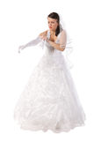 Bride dressed in dress gets into long gloves Royalty Free Stock Photography