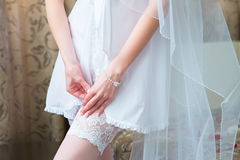 Bride dresses garter on the leg. Picture of beautiful female bar Royalty Free Stock Photography
