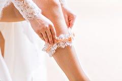 Bride dresses garter on the leg Royalty Free Stock Photo