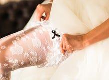 Bride dresses garter on the leg Stock Photo