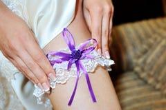 Bride dresses garter on the leg Stock Photography