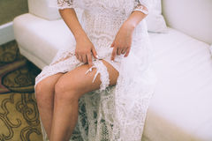 Bride dresses garter on the leg. Picture of beautiful female barefoot legs in wedding dress Royalty Free Stock Image