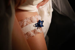 Bride dresses garter on the leg. Picture of sexy female barefoot legs in wedding dress Stock Image