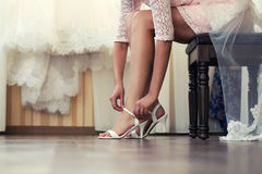Bride Dresses shoes. Bride puts his shoes in the morning in the interior Royalty Free Stock Photography
