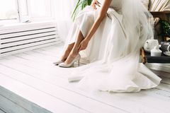 Bride dresses shoes before the wedding ceremony. Charges of the bride. Closeup detail of bride putting on high heeled sandal. Wedding shoes. Wedding bride shoes royalty free stock photos