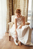 Bride dresses shoes. Before the wedding ceremony. The bride on her wedding day. Concept of bride morning. Bride puts on white shoes on feet. Bride fitting shoes stock images