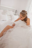 Bride dressing putting on garter stock photography