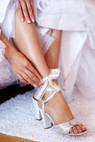 Bride dressing shoes. Leg of young woman in shoes Stock Photo