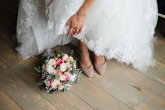 Bride dressing shoes. Leg of young woman in shoes stock images