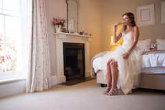 Bride drinking champagne while sitting on bed Royalty Free Stock Photography