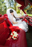Bride driving a car. Bride driving convertible car with bouquet of flowers on front seat outdoors Stock Photo