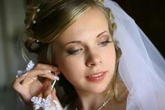 Bride with earring. Portraint of a young beautiful bride wearing earring Royalty Free Stock Photo
