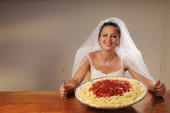 Bride eats spaghetti. Young bride eats spaghetti with tomato in rustic setting Royalty Free Stock Images