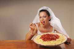 Bride eats spaghetti. Young bride eats spaghetti with tomato in rustic setting Stock Photography