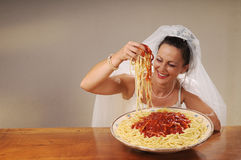 Bride eats spaghetti. Young bride eats spaghetti with tomato in rustic setting Stock Photos