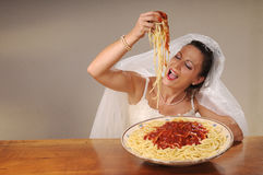 Bride eats spaghetti. Young bride eats spaghetti with tomato in rustic setting Royalty Free Stock Photos