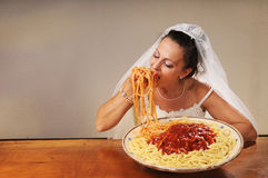 Bride eats spaghetti. Young bride eats spaghetti with tomato in rustic setting Royalty Free Stock Photography