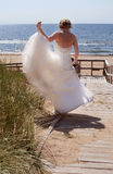A Bride on the Edge. A young bride dressed in a white wedding gown from behind holding her gown with one hand as she walks on the edge of a ramp leading down to Stock Photos