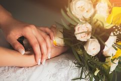 The bride in an elegant openwork wedding dress is holding a beautiful wedding bouquet of white or beige roses and green leaves. royalty free stock photo