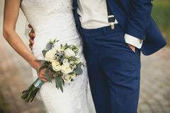 The bride in an elegant wedding dress is holding a beautiful bouquet of white roses, buds, green leaves and decorative items. stock photography