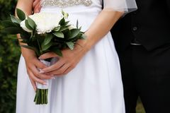 The bride in an elegant wedding dress is holding a beautiful bouquet of white roses and chrysanthemums and green leaves. Embrace royalty free stock photography