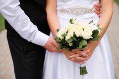 The bride in an elegant wedding dress is holding a beautiful bouquet of white roses and chrysanthemums and green leaves. Embrace stock image