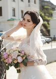 bride in elegant wedding dress posing outdoor with tender bouquet of flowers royalty free stock images