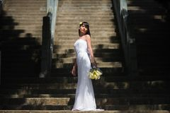 Bride in an elegant wedding dress stands on the background of a large staircase royalty free stock images