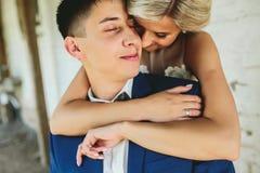 Bride embraces bridegroom Stock Photo