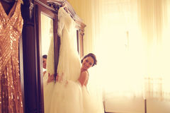 Bride embracing her wedding dress at home Stock Images