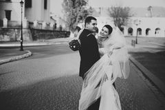 Bride encloses a groom in her veil while he hugs her Royalty Free Stock Photography