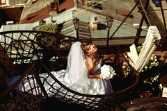 Bride enjoys summer sun standing on the spiral stairs on the roo. F Stock Photo
