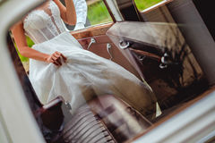 Bride entering classic car and holding dress Stock Photos