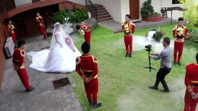 Bride escorted to wedding chariot by uniformed attendants. San Pablo City, Laguna, Philippines - August 7, 2016: Bride being escorted by uniformed attendants to stock video