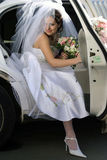 Bride exiting wedding car limo. Smiling bride with bouquet exiting her wedding car limousine Royalty Free Stock Images