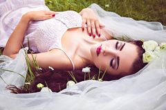 Bride with eyes closed lying on blooming meadow Royalty Free Stock Photo