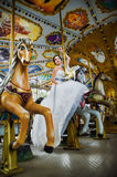 Bride on a fairground carousel ride. Bride in white dress rising a horse on traditional fairground carousel ride Stock Photos