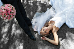 Bride is falling at groom's feet Royalty Free Stock Image