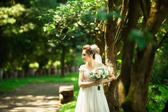 Bride in fashion wedding dress on natural background. A beautiful woman portrait in the park royalty free stock images