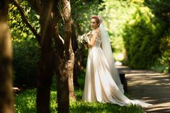 Bride in fashion wedding dress on natural background. A beautiful woman portrait in the park. Back view royalty free stock photography