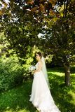 Bride in fashion wedding dress on natural background. A beautiful woman portrait in the park stock photos