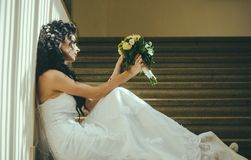 Bride in fashion white dress. Sensual woman with wedding bouquet. Woman with flowers sit on staircase. Girl with bridal Royalty Free Stock Photography