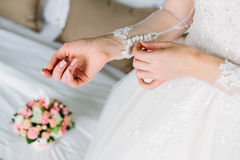 Bride is fasten sleeves on her dress, preparing for the wedding day. Close up Royalty Free Stock Photography